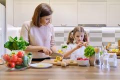 在家一起烹调在厨房里的母亲和孩子 健康吃,母亲教女儿烹调,父母儿童通信 免版税库存图片