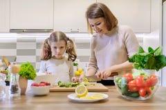 在家一起烹调在厨房里的母亲和孩子 健康吃,母亲教女儿烹调,父母儿童通信 免版税库存照片