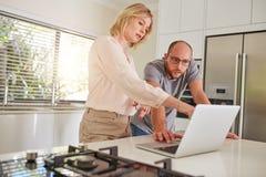 在家一起研究膝上型计算机的成熟夫妇 免版税图库摄影