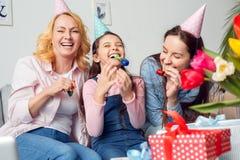 在家一起祖母坐与党吹风机的母亲和女儿生日获得乐趣 免版税库存照片