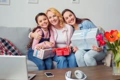 在家一起祖母坐与礼物的母亲和女儿庆祝拥抱微笑 图库摄影