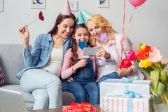 在家一起祖母坐在欢乐盖帽的母亲和女儿庆祝拥抱拍selfie照片与 图库摄影