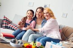 在家一起祖母坐母亲和女儿的庆祝拥抱笑快乐 免版税库存照片