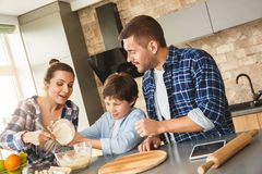 在家一起站立在加面粉的厨房母亲帮助的儿子的桌上的家庭滚保龄球快乐 免版税图库摄影