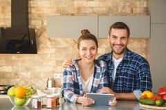 在家一起站立在厨房丈夫的年轻夫妇拥抱拿着数字片剂的妻子看照相机愉快 免版税图库摄影