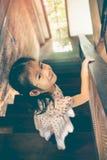 在家下来亚裔的女孩微笑和木台阶 Vintag 库存图片