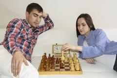 在家下棋的轻松的年轻夫妇说谎在沙发 赢取-友谊 免版税库存图片