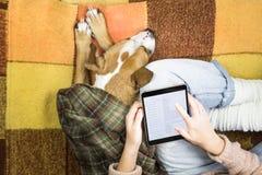 在家与片剂一起使用在睡觉狗旁边 免版税图库摄影