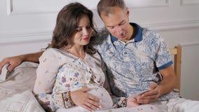 在家举行他们期望的婴孩的超声波扫描年轻微笑的夫妇 股票视频