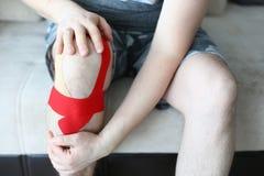 在家举行在长沙发的男性手sored膝盖开会 免版税库存照片