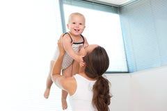 在家举逗人喜爱的婴孩的愉快的母亲 免版税图库摄影