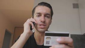 在家买网上用途的愉快的年轻人电话和信用卡厨房购物互联网用途智能手机 影视素材