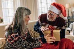 在家交换圣诞礼物的资深夫妇 免版税库存图片