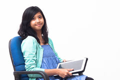 拿着她的片剂个人计算机的被隔绝的微笑的年轻女商人 图库摄影