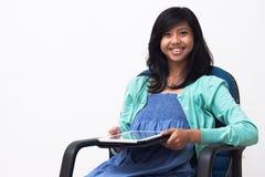 拿着她的片剂个人计算机的被隔绝的微笑的年轻女商人 免版税库存图片