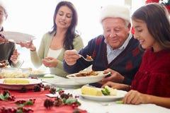 在家享受圣诞节膳食的多一代家庭 库存照片