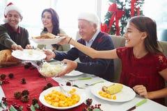在家享受圣诞节膳食的多一代家庭 免版税图库摄影
