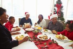 在家享受圣诞节膳食的多一代家庭 免版税库存图片