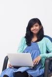 拿着膝上型计算机和享受她的工作的年轻女商人 免版税库存照片