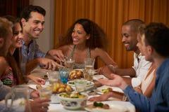 在家享受晚餐会的小组朋友一起 库存照片