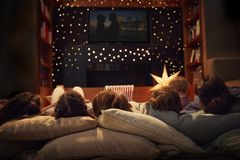 在家享受电影之夜的家庭一起 免版税库存照片