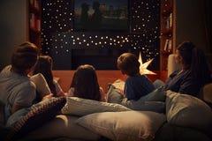 在家享受电影之夜的家庭一起 免版税库存图片