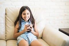 在家享受软饮料的快乐的女孩 免版税图库摄影