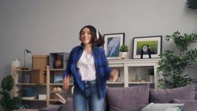 在家享受音乐跳舞的无忧无虑的学生唱歌在遥控 股票录像