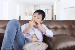 在家享用乳酪汉堡的逗人喜爱的男孩 免版税库存照片