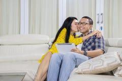 在家亲吻她的丈夫的少妇 免版税库存图片