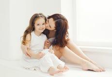 在家亲吻女儿的爱恋的母亲在绝尘室 库存图片