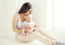 在家亲吻她的婴孩的年轻妈妈在轻的屋子里 图库摄影