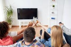 在家使啤酒叮当响和看电视的朋友 免版税库存照片