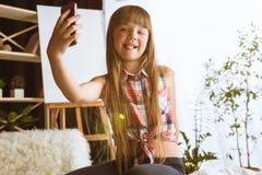 在家使用不同的小配件的女孩 图库摄影