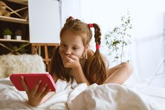 在家使用不同的小配件的女孩 库存图片