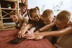 在家使用不同的小配件的小男孩和女孩 库存图片