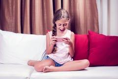 在家使用与一个手机的小女孩在沙发 免版税库存照片