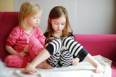 在家使用与一种数字式片剂的两个孩子 免版税图库摄影