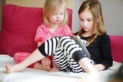 在家使用与一种数字式片剂的两个孩子 免版税库存图片