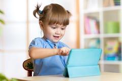 在家使用与一种数字式片剂的儿童女孩 库存照片