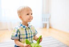 在家使用与乘驾在玩具的愉快的男婴 库存图片