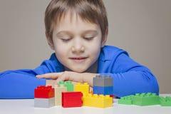 在家使用与五颜六色的塑料建筑砖的小孩男孩 库存照片