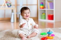 在家使用与五颜六色的玩具的逗人喜爱的快乐的婴孩 库存图片