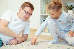 在家使用与他逗人喜爱的矮小的女儿的愉快的年轻父亲 免版税库存照片