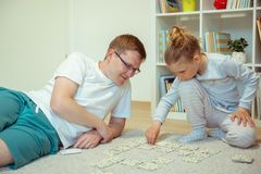 在家使用与他逗人喜爱的矮小的女儿的愉快的年轻父亲 库存照片
