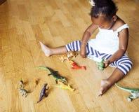 在家使用与动物玩具的小逗人喜爱的非裔美国人的女孩,相当内部愉快微笑的可爱的公主 库存图片