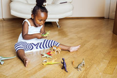 在家使用与动物玩具的小逗人喜爱的非裔美国人的女孩,相当内部愉快微笑的可爱的公主 免版税库存图片