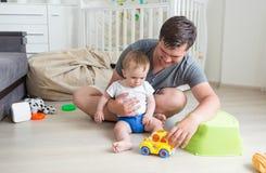年轻在家使用与在地板上的玩具汽车的父亲和他的男孩 免版税库存图片