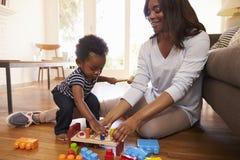在家使用与在地板上的玩具的母亲和儿子 图库摄影