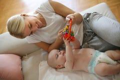 在家使用与她的小男婴的愉快的母亲 库存图片